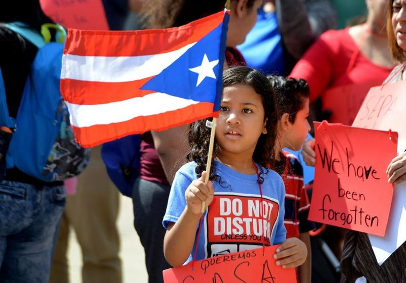 Puerto Rican families displaced by hurricanes last year and relocated to Western Massachusetts seek help from Senators Elizabeth Warren and Ed Markey and are trying to deliver messages to their offices in Springfield, Massachusetts.