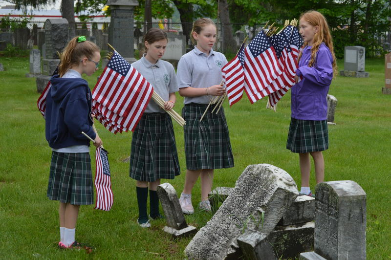 Blessed Sacrament students Dara Cassidy, Siobhan Armstrong, Molly Smith and Gracie Chesmore place flags on graves belonging to veterans at Cavalry Cemetery in Holyoke, Massachusetts.