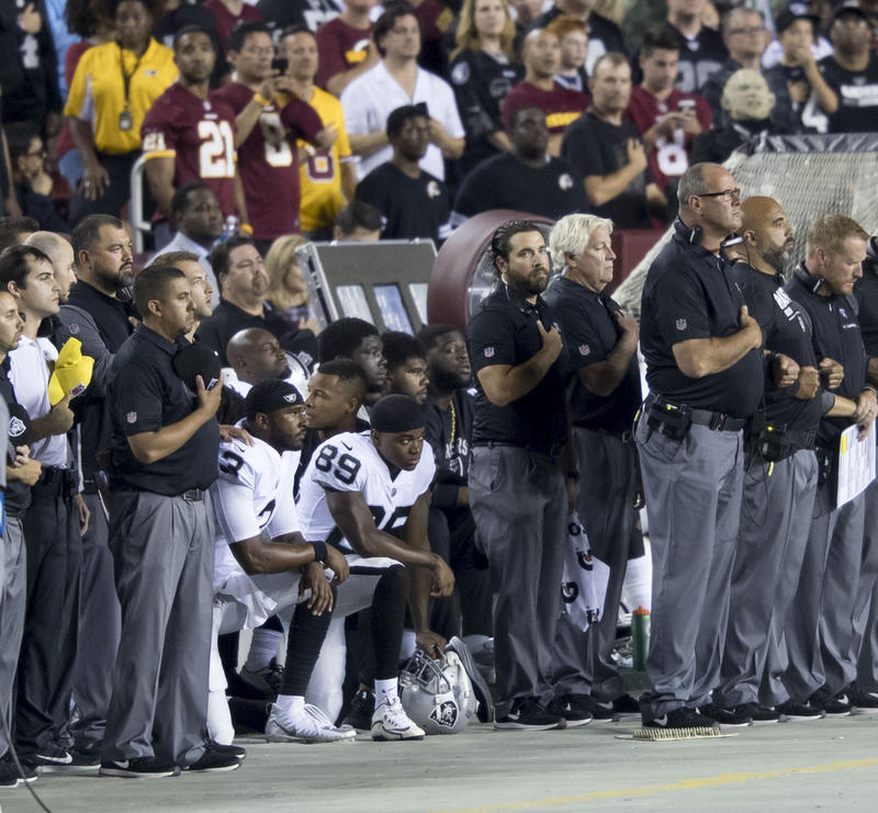 Oakland Raiders teammates kneel during the national anthem before a game against the Washington Redskins at FedExField on September 24, 2017 in Landover, Maryland.