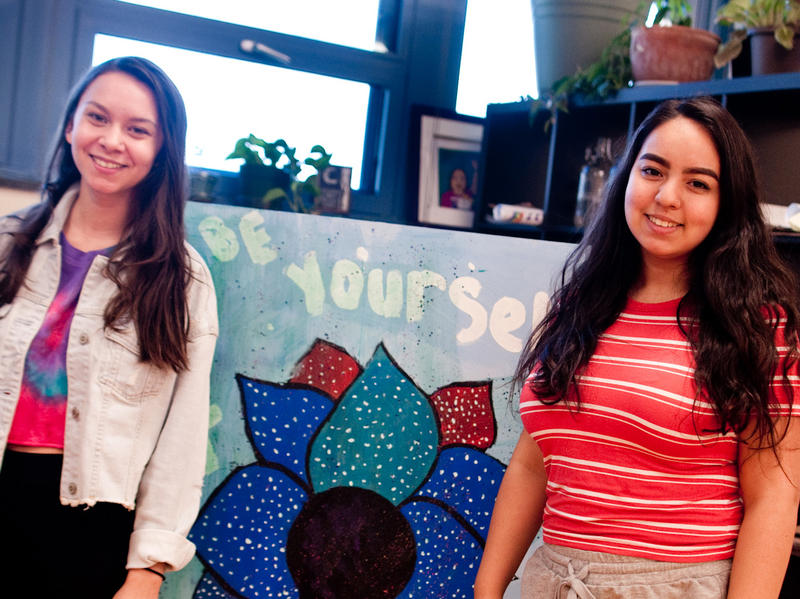 Emily Rodriguez, a sophomore, and Vianca Gonzalez, a senior, are peer leaders in Pa'lante. They stand next to artwork in the student support room, which the program transformed in 2015 through one of their