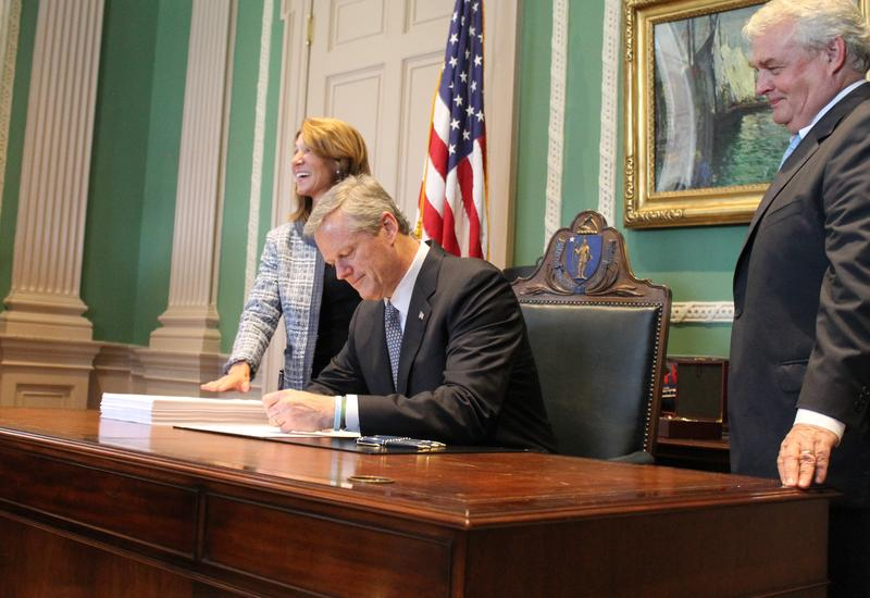 Massachusetts Governor Charlie Baker signs the fiscal 2019 budget in his office alongside Lt. Gov. Karyn Polito and Administration and Finance Secretary Mike Heffernan.