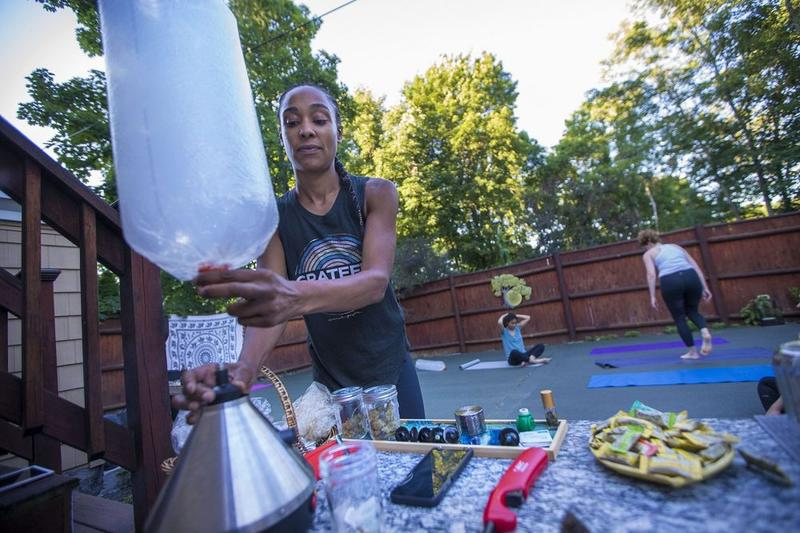 Kijana Rose fills a plastic balloon with marijuana vapor for one of her Beginners Ganja Yoga Flow students.