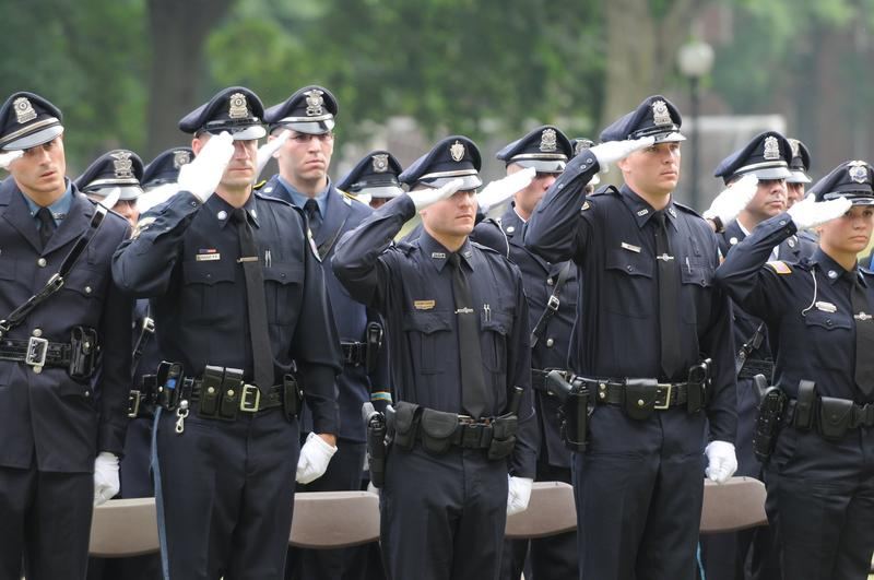 New police officers from western Massachusetts salute during a graduation ceremony at the Police Training Academy at Springfield Technical Community College in 2010.