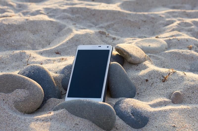 A mobile phone on a sandy beach.