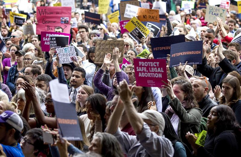 Protesters at an October 1, 2018, Boston rally hold up #stopkavanaugh signs.