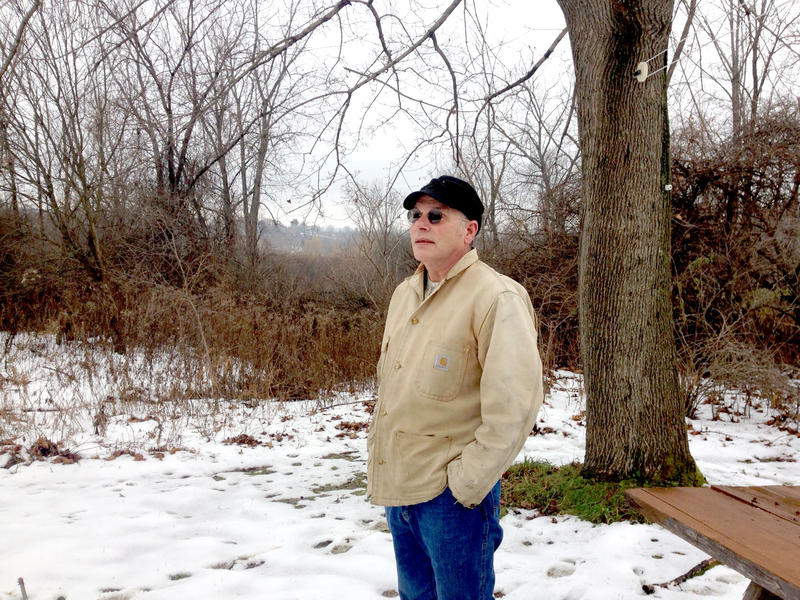 Anthony Coniglio stands in his yard in North Adams, Massachusetts. A proposed bike path would be built behind him. He says it would impinge on his privacy and will fence out wildlife like bear and bobcat.