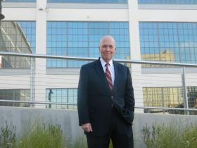 "Gary Green, ED.D., president of Forsyth Technical Community College stands in front of the school's future Center for Emerging Technologies at Wake Forest Innovation Quarter. The former ""90 series"" R.J. Reynolds Tobacco Company building is being renovated for the project."