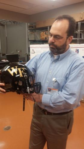 Dr. Joel Stitzel displays a specialized football helmet fitted with accelerometers.