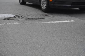 The City of Greensboro invites residents to report the location of potholes so road crews can fix them.