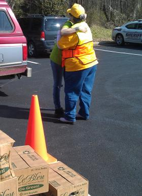 A volunteer at Pleasant Garden Baptist Church gets a hug from a resident in the aftermath of the March ice storms. The church worked with the American Red Cross to offer free bottled water to the community.