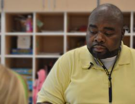 Anthony Freeman, a teacher assistant at E.P. Elementary School in Greensboro, helps students with an exercise in phonics on Tuesday, June 3, 2014.