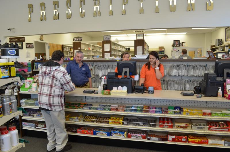 David Marley (behind counter in blue shirt) talks with a customer about their prescription at Marley Drugs in Winston-Salem.