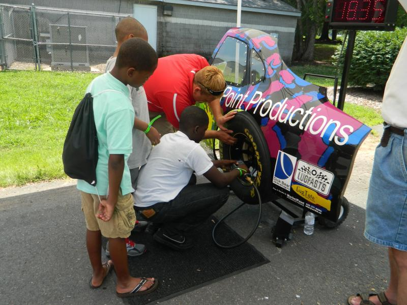 A student at Winston-Salem State University shows kids how to change a tire in 14 seconds during the camp on Tuesday at the Rupert Bell Neighborhood Center in Winston-Salem..