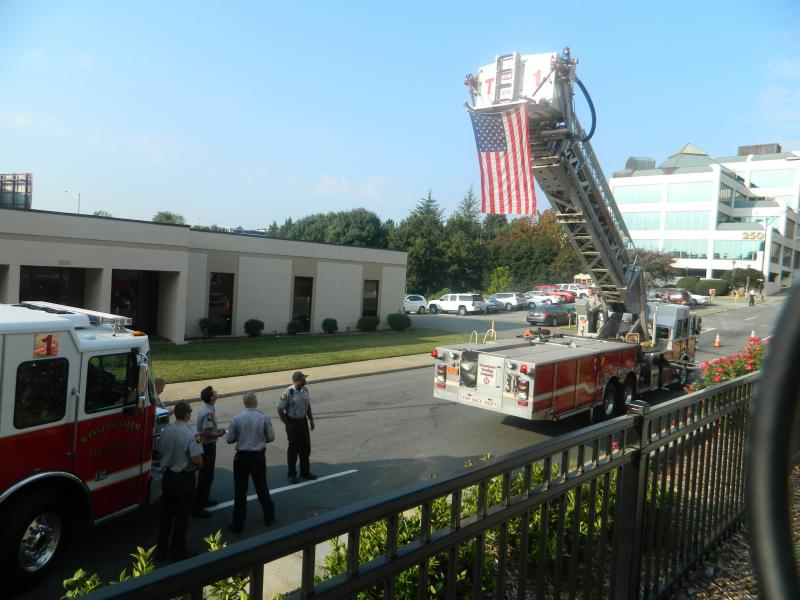 Members of the Winston-Salem Fire Department proudly display Old Glory during the commemeration at Corpening Plaza on Wednesday.