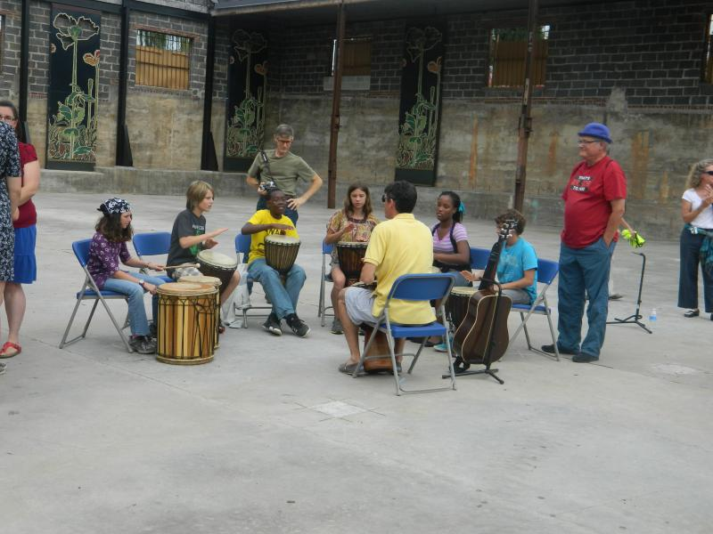 Students at the Arts Based School practice their African drumming performance before the ribbon cutting on Thursday.