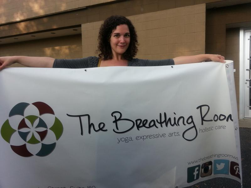 Emily Stewart holds up The Breathing Room's sign.