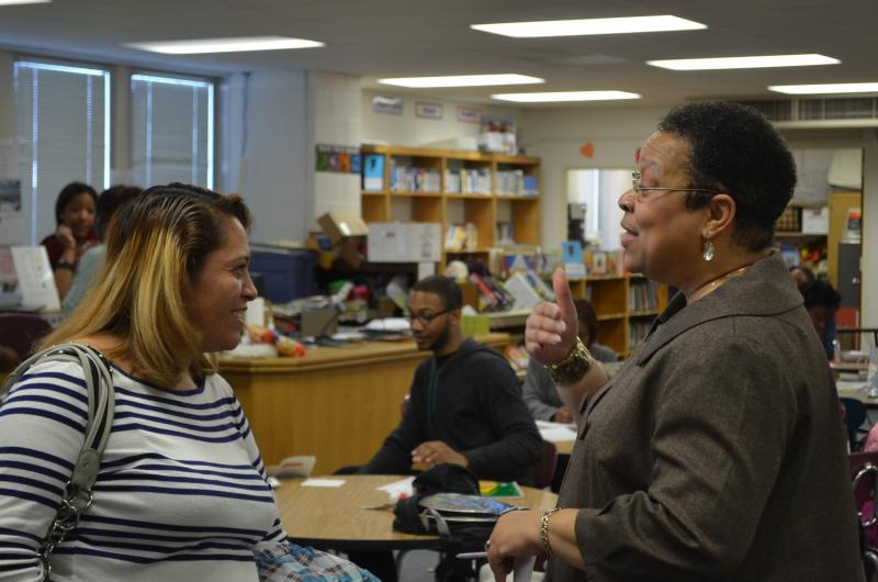 Dr. Kim Pemberton (r) explains to Teresa Azcorra (l) how the I-Rise Literacy Academy will help her daughter, Jazury, develop stronger reading skills.