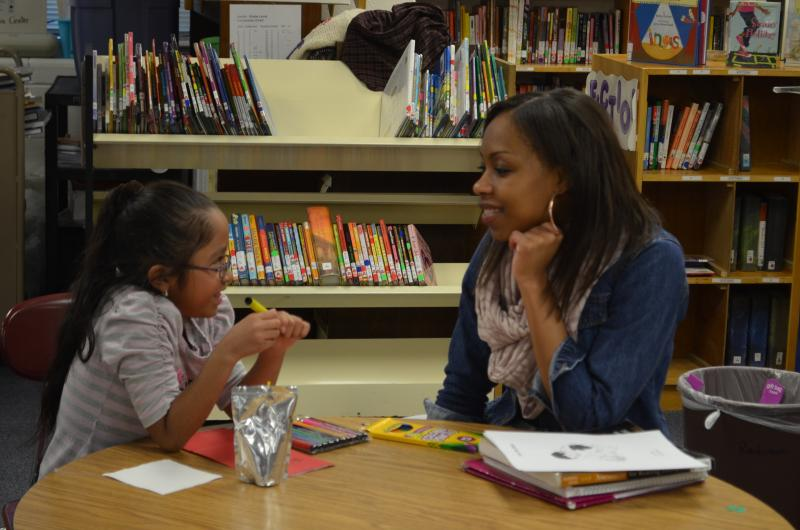 First grader Jazury Salinas explains the story she just read to her WSSU tutor Jasmine Wright at Easton Elementary School. Jazury's mother wants her daughter to be fluent in English.