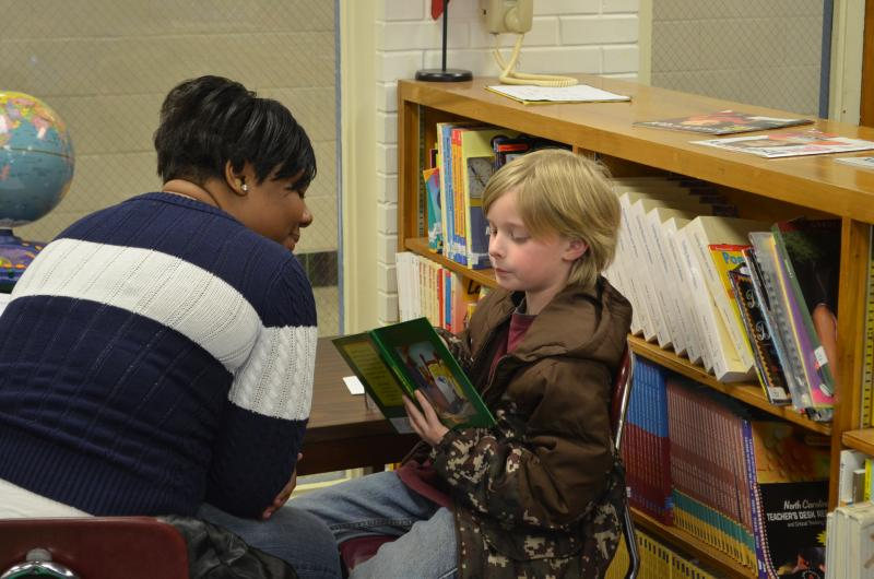 18 Education majors from Winston-Salem State University are tutoring first and second grade students at Easton Elementary School in reading comprehension and fluency. Erika Wright (r) helps second grader Ryder Lynch.