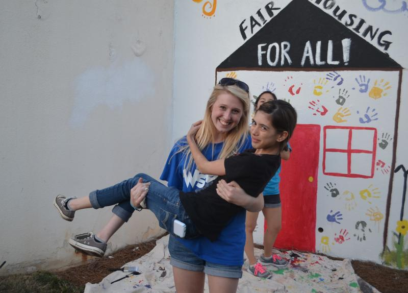Anna Glover (l) and Asia Catral (r) take a break from painting their 2014 mural.