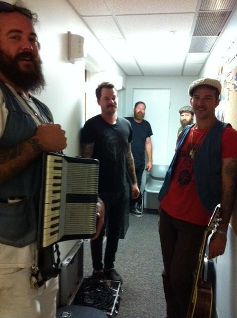 The Drowning Men crowded into the hallway with their instruments post-studio session.