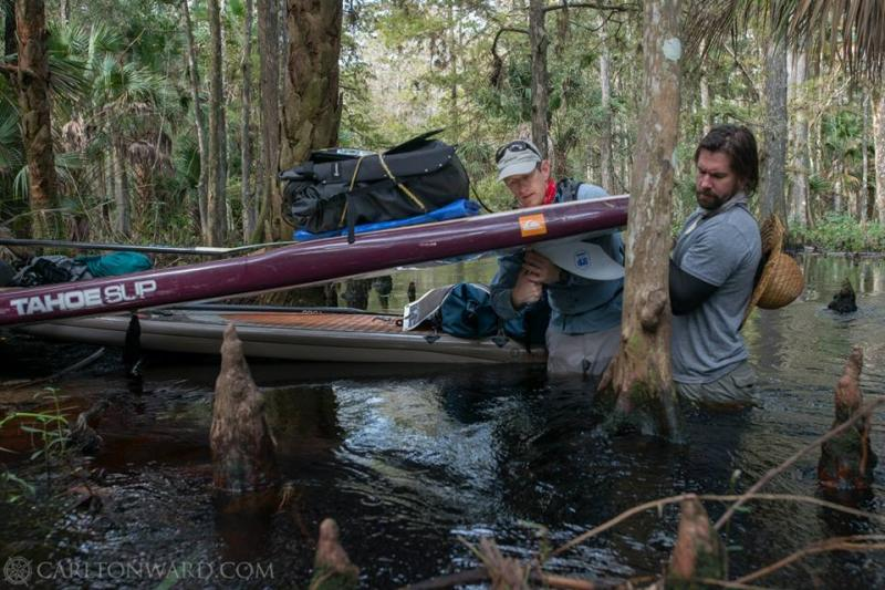 Carlton Ward Jr. and Justin Riney remove the fins from their boards to avoid snagging cypress knees and submerged branches.