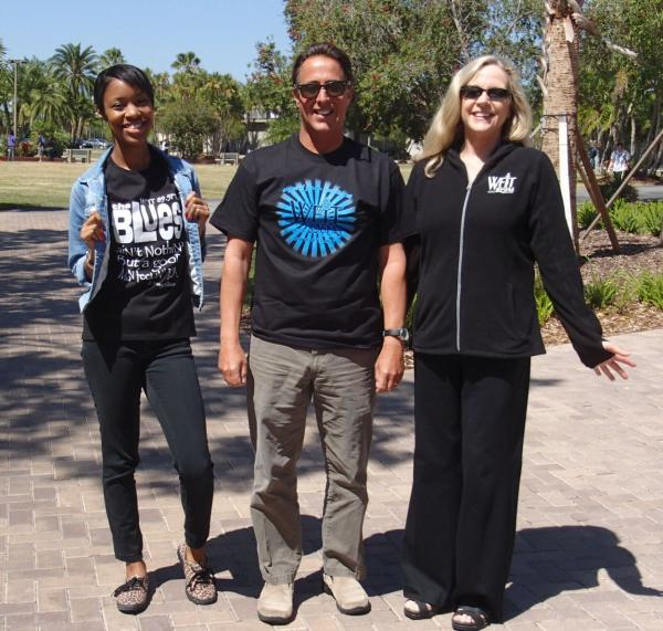Tia, along with Sound Waves host, Todd Kennedy, and Director of Outreach, Rose Mantle, bask in the rays while sporting their WFIT gear.