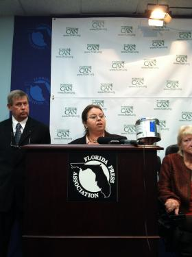 Florida Cannabis Action Network Executive Director  Jodi James holds a canister that the federal government uses to ship marijuana cigarettes to Irvin Rosenfeld.