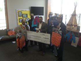 Ahmed Temple No. 37 Shriners present a $750 check along with 50 new winter coats to Riley Elementary School Principal Karwynn Paul.