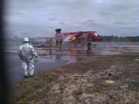 """Tallahassee Airport fire crews extinguish """"aircraft"""" fire as Trainer Allen Fine looks on."""