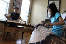 Florida Folklife Master Haiqiong Deng practices a zheng duet with apprentice Crystal Zhang before the Florida Folk Festival.
