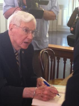 Former Governor Reubin Askew autographs a copy of a book about his life as a politician.