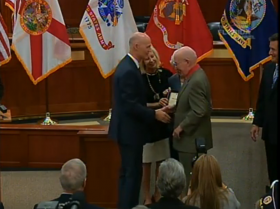 Florida Governor Rick Scott congratulates Veterans Hall of Fame inductee John Cleland.