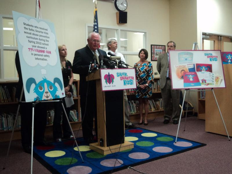 "Senator Bill Montford speaking at the ""Safer, Smarter Kids"" Conference. Lauren Book and Superintendent of Leon County Schools Jackie Pons are on both sides of him along with Florida Department of Children and Families Secretary David Wilkins (far left)."