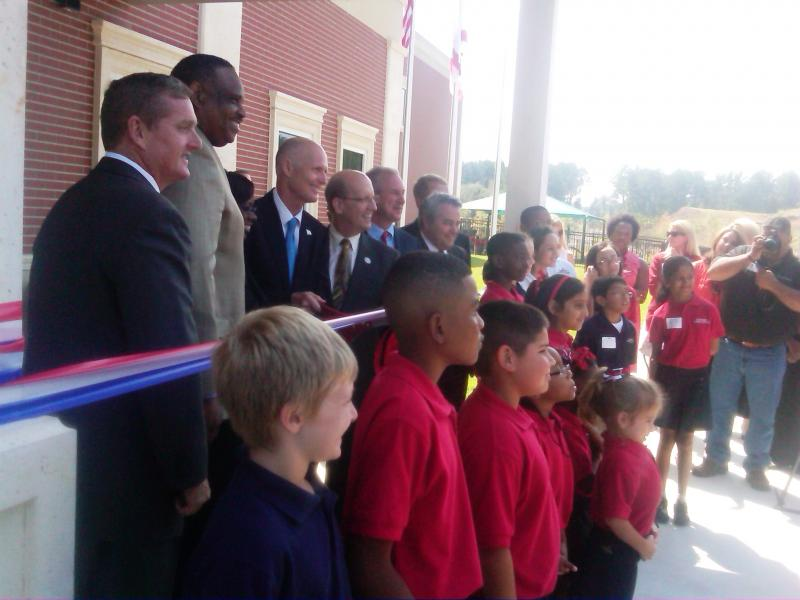 Gov. Rick Scott (center) joins Al Lawson (center left) and others in a ribbon-cutting ceremony for Governors Charter Academy