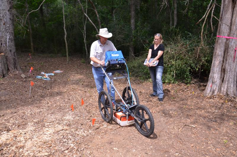 Archeologist  Rich  Estabrook  guides  the  Ground  Penetrating  Radar   as  USF  Anthropologist  Erin  Kimmerle  watches  the  results.