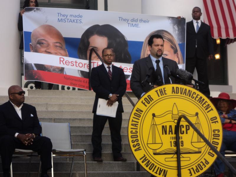 NAACP President and CEO Benjamin Jealous speaking on the steps of the old Florida Capitol with Actor Charles Dutton looking on (far left)