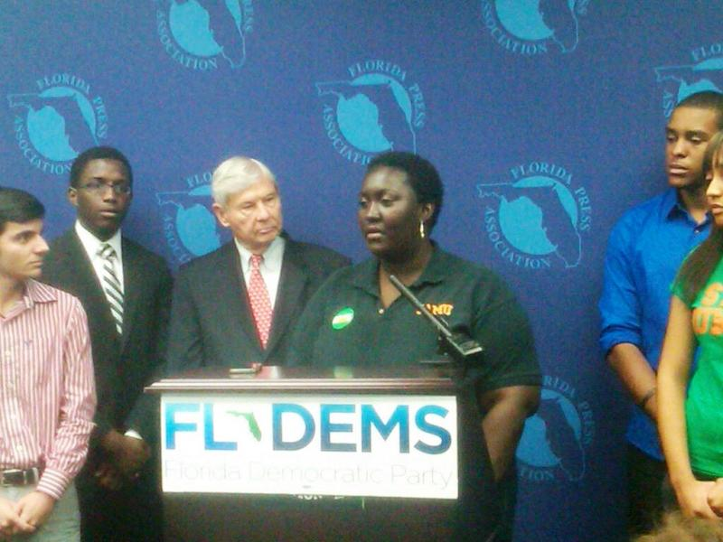 Kamaria Jackson (center) stands with former Gov. Bob Graham (left). Democrats are attacking Republicans over tuition hikes and higher education budget cuts.