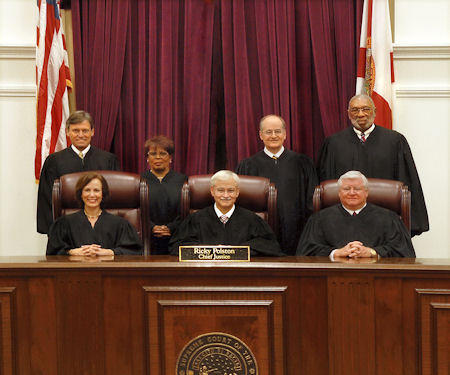 The seven-member Florida Supreme  Court poses for a photo in the courtroom.