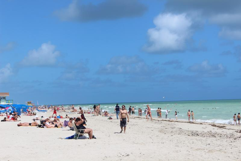 Sunbathers enjoy Miami Beach in October 2012. Scientists say the ocean level is rising at a rate of one-tenth of an inch per year and will rise more quickly in the future.