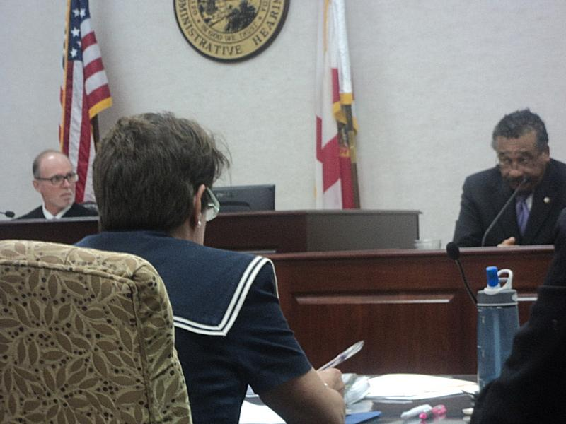 Administrative Law Judge Lawrence Stevenson listening to Tallahassee Mayor John Marks, as he answers questions from Diane Guillemette, chief advocate for the Florida Commission of Ethics