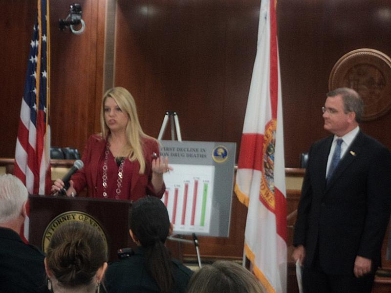 Florida Attorney General Pam Bondi talking at a press conference about the decline in prescription drug deaths, while Florida Surgeon General Dr. John Armstrong looks on.