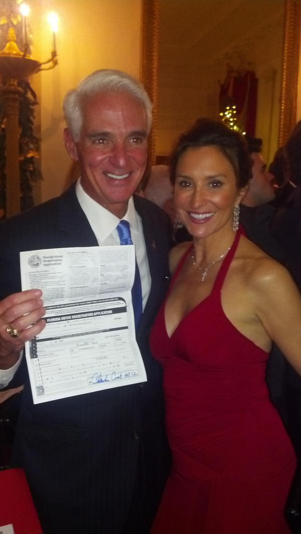 Former Republican Governor Charlie Crist holding his form that shows he registered as a Democrat.