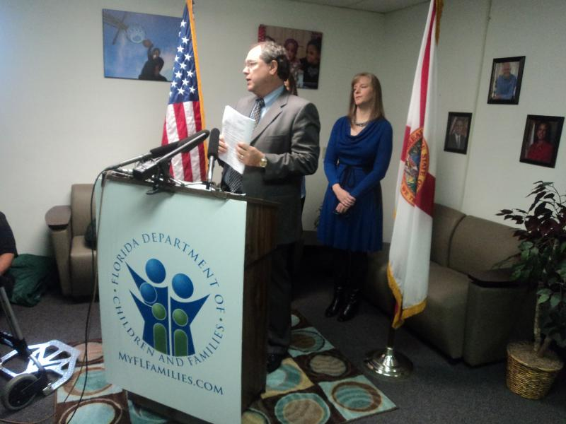 Florida Department of Children and Families Secretary David Wilkins showing an example of the paperforms hotline workers used to have to fill out.
