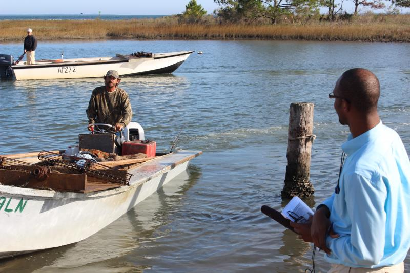 Eric Evans bringing his boat to shore as Trimmel Gomes waits to interview him.
