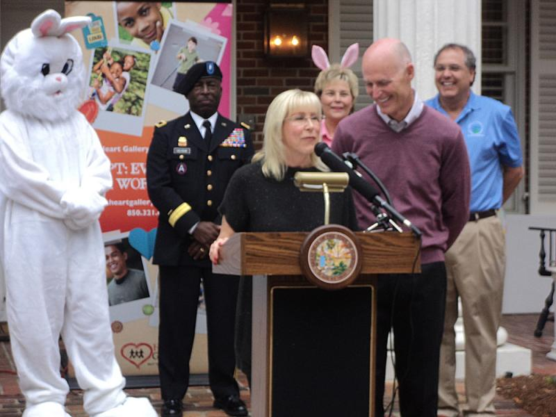 First Lady Ann Scott talking at the Easter event next to Governor Scott. Behind her is the Easter Bunny, Florida National Guard Brigadier Gen. Michael Calhoun, APD Director Barbara Palmer, and DCF Sec. David Wilkins.