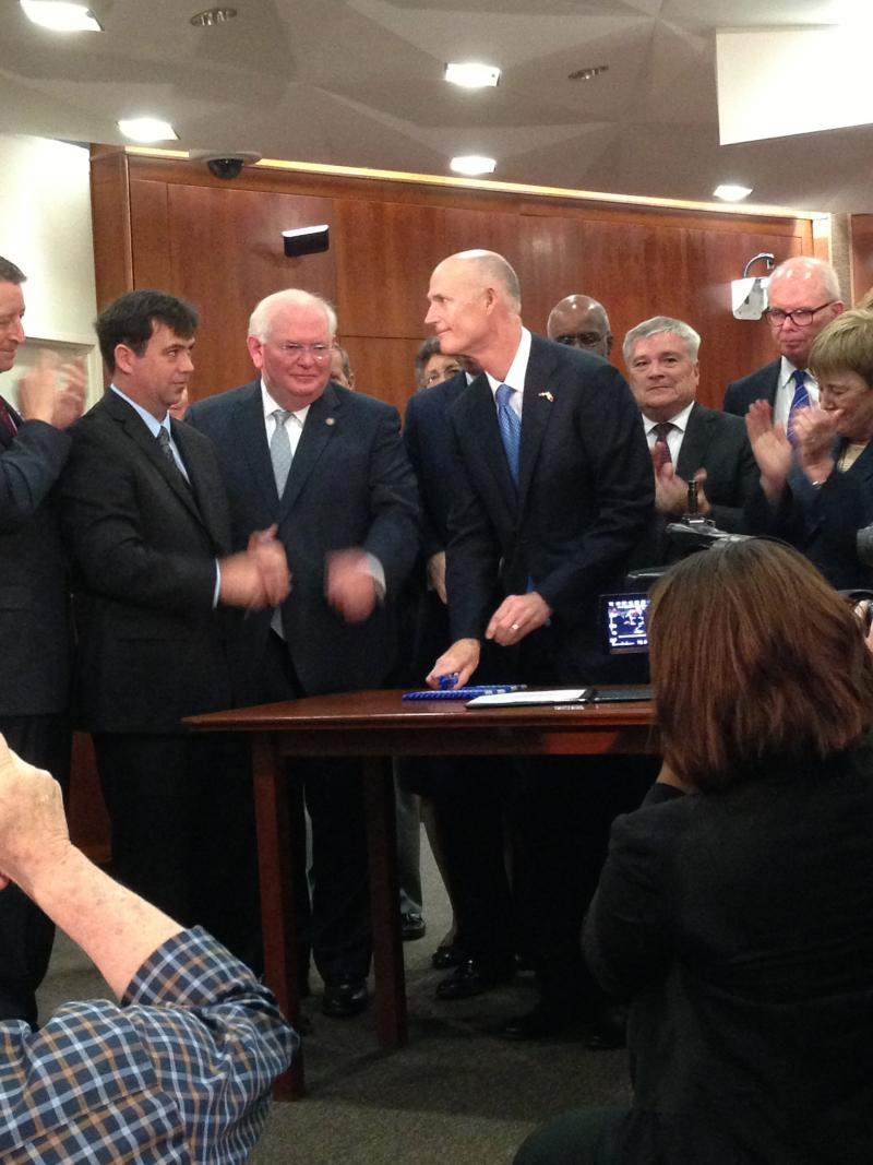 Gov. Rick Scott shakes hands after signing the education overhaul bill