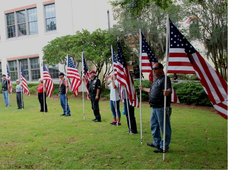 Patriot Guard Riders hold American flags during the ceremony.