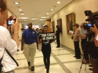 "A protester walks into the governor's office carrying a sign that reads: ""the state is ours."""