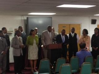 Pastor R.B. Holmes addresses reporters on Thursday